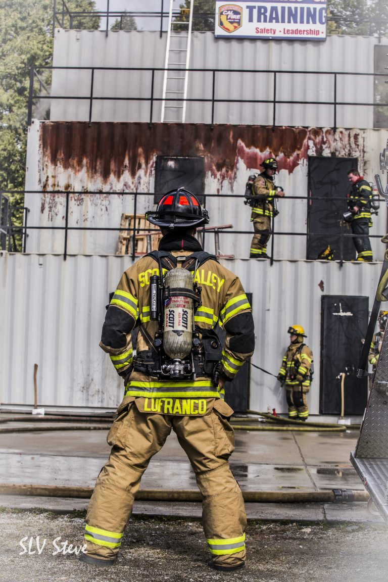 Scotts Valley Firefighter dressed in turnouts supervising other firefighters train